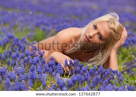 Beautiful blond  girl with violet spring flowers, amazing spring photo from Latvia, Baltic states, Europe - stock photo