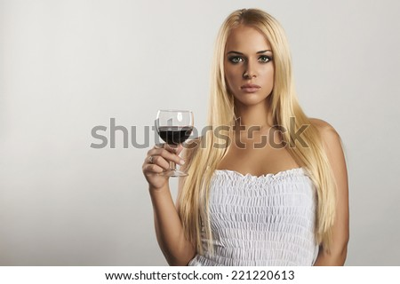 Beautiful blond girl with wineglass.girl in blue dress.dry red wine.sexy young woman with alcohol. your text here - stock photo