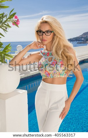 Beautiful blond hair sexy woman young girl model in sunglasses and elegant color  with crystals sweatshirt, top around the pool with a balustrade overlooking the sea and the island of Santorini - stock photo