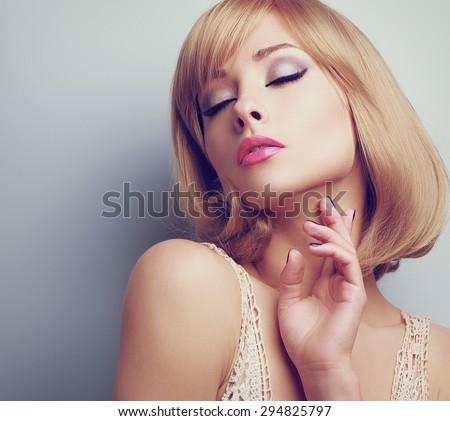 Beautiful blond hair woman with closed makeup eyes touching neck perfect skin. Toned closeup portrait - stock photo