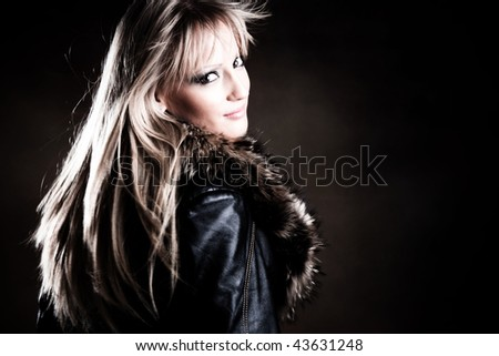 beautiful blond in leather jacket in motion - stock photo