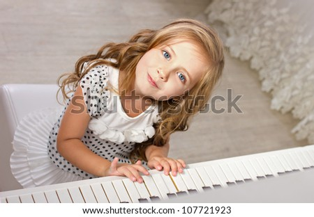 beautiful blond little girl with blue eyes in pretties sitting near a piano and  looking at camera - stock photo