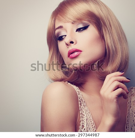 Beautiful blond makeup woman with short hair style looking down. Toned color closeup portrait with empty copy space - stock photo