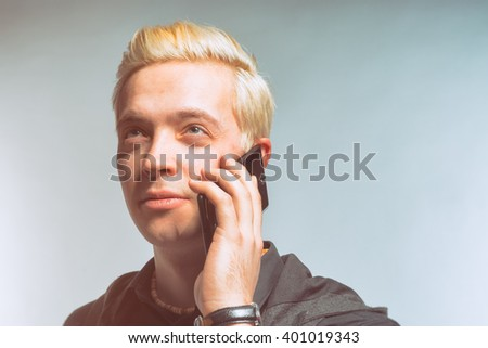 Beautiful blond man dressed in black talking on the phone. Toned - stock photo