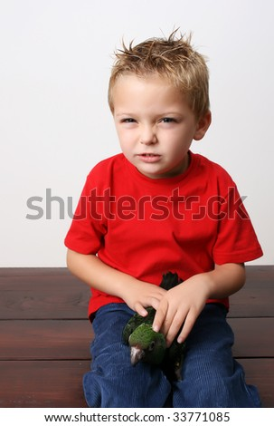 Beautiful blond toddler holding his parrot on his lap - stock photo