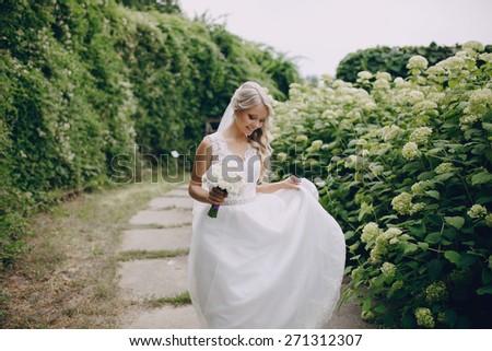 beautiful blond wedding couple walking on reserve - stock photo