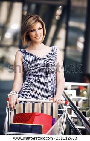 Beautiful blond with shopping cart near supermarket - stock photo