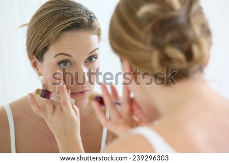 Beautiful blond woman applying concealer around eyes - stock photo
