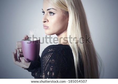 Beautiful blond woman drinking Coffee. Cup of tea. Hot drink. Black dress - stock photo