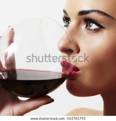 Beautiful blond woman drinking red wine.make-up.red lips.wineglass - stock photo