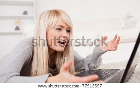 Beautiful blond woman frustrated with her computer lying on a carpet in the living room - stock photo
