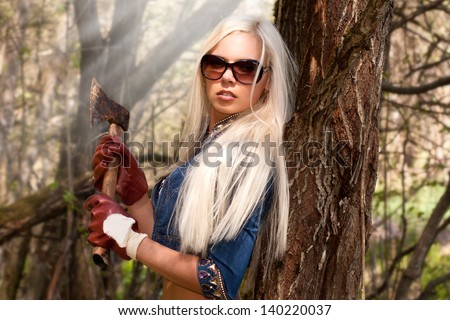 Beautiful blond woman holding an axe in the forest - stock photo