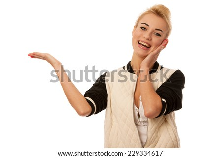 Beautiful blond woman holding hand over white copy space for promotional purpose - stock photo