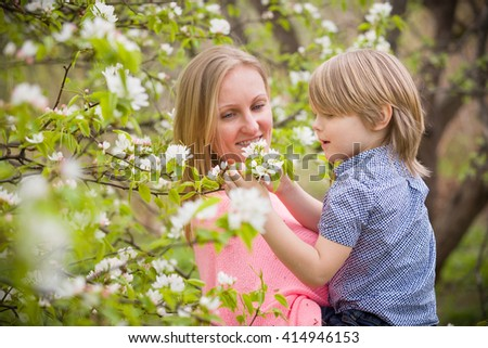 Beautiful blond woman holding her little adorable kid boy in the blooming park on a sunny spring day. Happy mother with her son enjoying apple trees flowers. Mum and child outdoors - stock photo