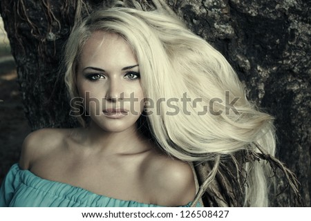 Beautiful blond woman in a forest - stock photo