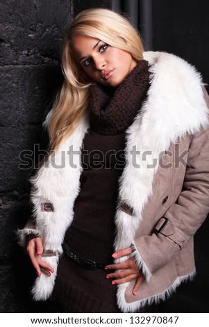 Beautiful blond woman in a fur near bricks wall - stock photo