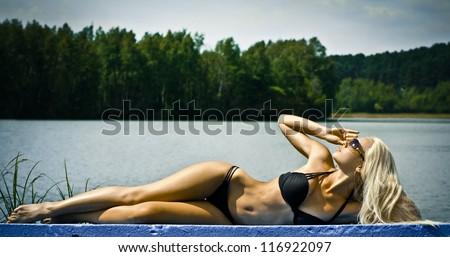 Beautiful blond woman in bikini at the beach - stock photo