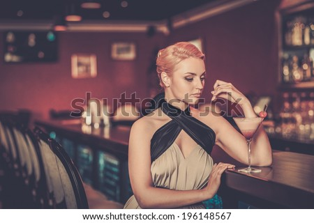 Beautiful blond woman in evening dress sitting near bar counter - stock photo