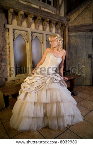 Beautiful blond woman in fairytale environment with wedding dress - stock photo