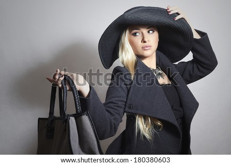 Beautiful Blond Woman in Hat. Fashionable Lady in Topcoat. Elegance Beauty Girl with Handbag. Spring Shopping - stock photo