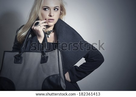 Beautiful Blond Woman in Topcoat. Fashionable Lady.Beauty Girl with Handbag. Spring Shopping - stock photo