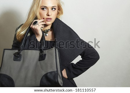 Beautiful Blond Woman in Topcoat. Fashionable Lady. Elegance Beauty Girl with Handbag. Spring Shopping - stock photo