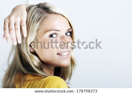 Beautiful blond woman looking back over her shoulder at the camera with a smile and her hand resting on her head, on white with copy space - stock photo