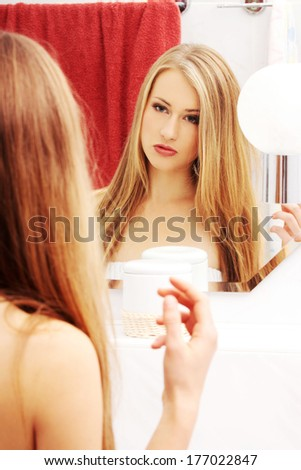 Beautiful blond woman looking in bathroom mirror  - stock photo