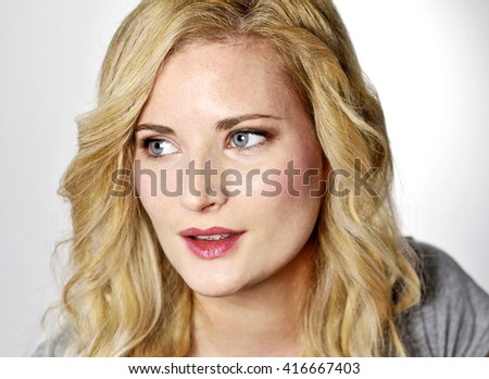 Beautiful blond woman looking to the side. Positive Emotions. Young woman with copy space, isolated on white background. - stock photo
