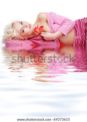 Beautiful blond woman lying on rose petals studio shot - stock photo