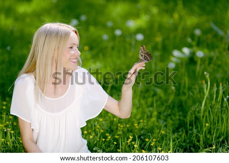 Beautiful blond woman playing with butterfly in spring park - stock photo