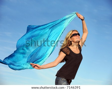 Beautiful blond woman running with a blue scarf - stock photo