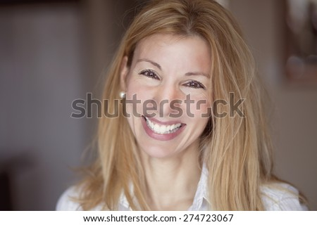 Beautiful blond woman smiling at the camera. She is confident and have a lot of leadership. - stock photo