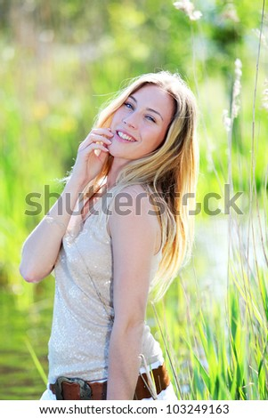 Beautiful blond woman standing in meadow with modern look - stock photo