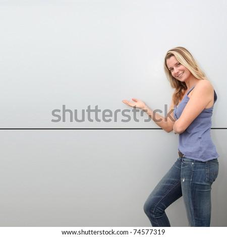 Beautiful blond woman standing on grey background - stock photo