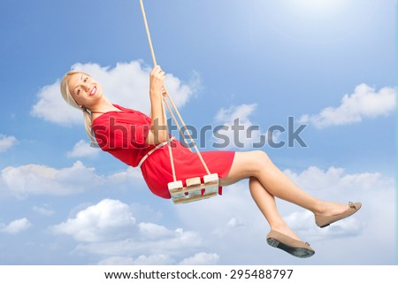 Beautiful blond woman swinging on a wooden swing outdoors on a beautiful summer day  - stock photo