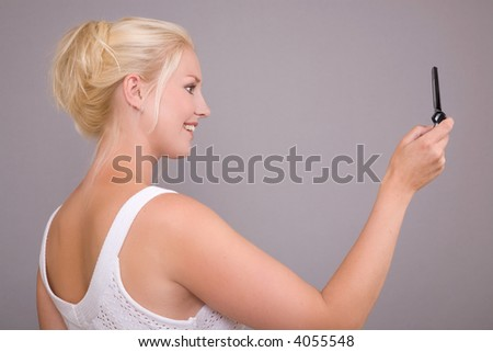 Beautiful blond woman taking a picture with her mobile phone - stock photo