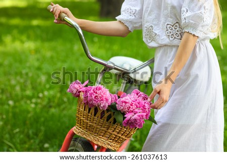 Beautiful blond woman wearing a nice dress in park with bicycle carrying a beautiful basket of peony flowers. Pretty blonde girl with retro look, bike and basket with flowers. Close up - stock photo