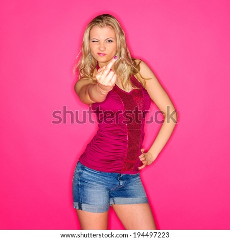 Beautiful blond woman wearing a red top and a denim shorts and posing against a pink studio background - stock photo
