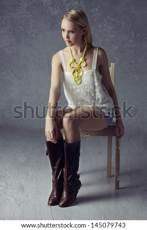 Beautiful blond woman wearing lace top, jean shorts, yellow necklace and leather boots on grunge studio background sitting on a rustic chair - stock photo