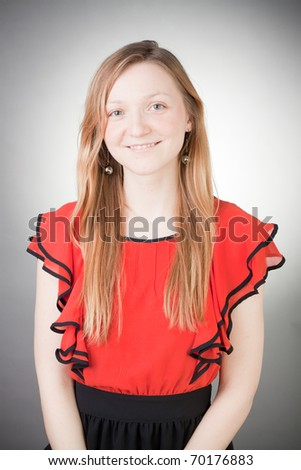 Beautiful blond woman wears red dress, with grey background - stock photo