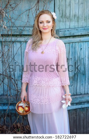 Beautiful blond woman with a basket of apples and flower petals - stock photo