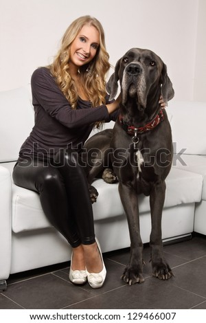 beautiful blond woman with a large dog  sitting on a white couch, she is dressed in leggings, shirt and shoes in the heel, interior photos, fashion photos, The dog is a Mastiff - stock photo