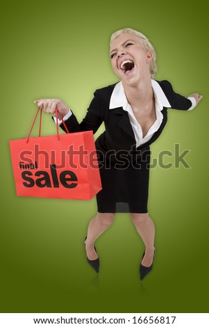 Beautiful blond woman with a red final sale shopping bag on a green isolated background - stock photo