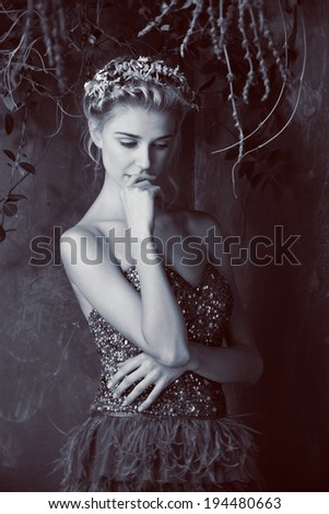 Beautiful blond woman with braid hairstyle and natural makeup. Wearing bohemian sequin and feather dress. Against grunge background. Vintage sepia effect - stock photo