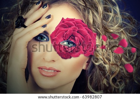 beautiful blond woman with curly hair wears a single rose flower as a mask around her eye, vintage effect - stock photo