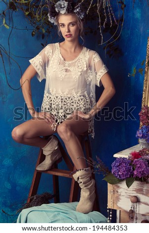 Beautiful blond woman with floral crown and natural makeup. Wearing lace white dress and boots. Against grunge blue background - stock photo
