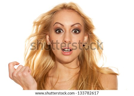 Beautiful blond woman with fluttering hair surprised - stock photo