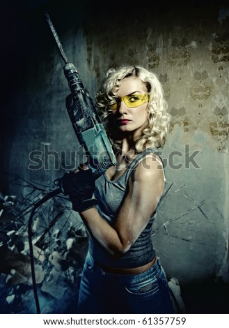 Beautiful blond woman with heavy drill in her hands - stock photo