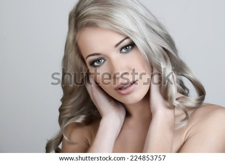 Beautiful blond woman with long curly hair - stock photo
